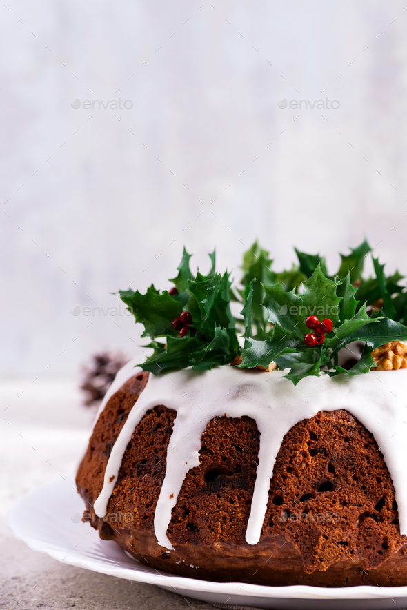 Christmas homebaked dark chocolate bundt cake decorated with white icing and holly berry branches - Stock Photo - Images