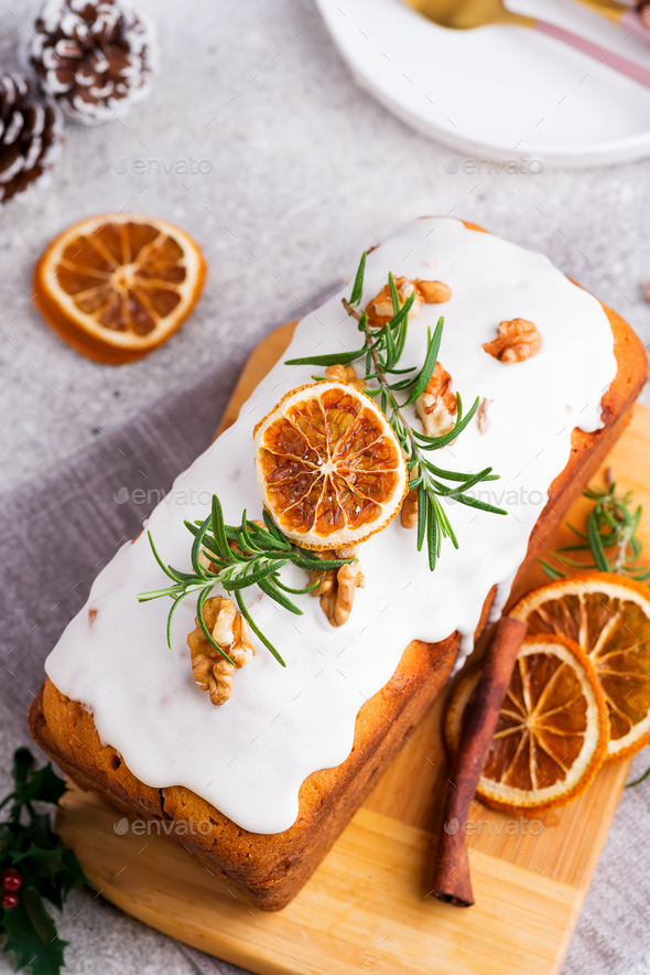 Fruit cake dusted with icing, nuts and dry orange on stone background, flat lay. Christmas and - Stock Photo - Images