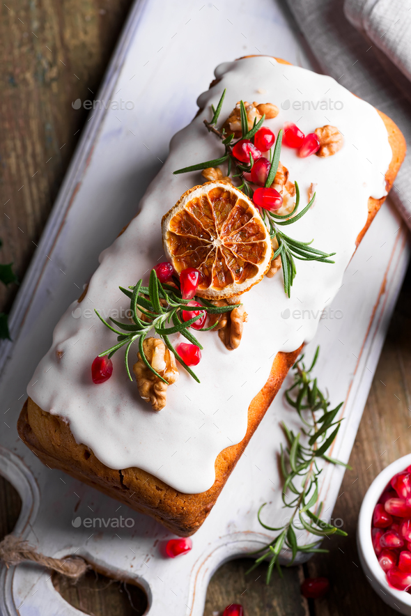 Fruit cake dusted with icing, nuts, kernels pomegranate and dry orange close-up. Christmas and - Stock Photo - Images
