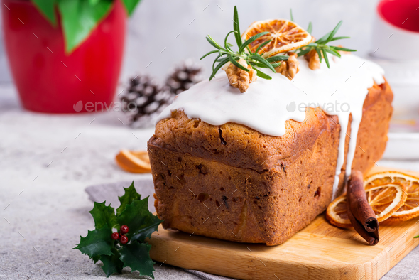 Fruit loaf cake dusted with icing, nuts and dry orange on stone background. Christmas and Winter - Stock Photo - Images