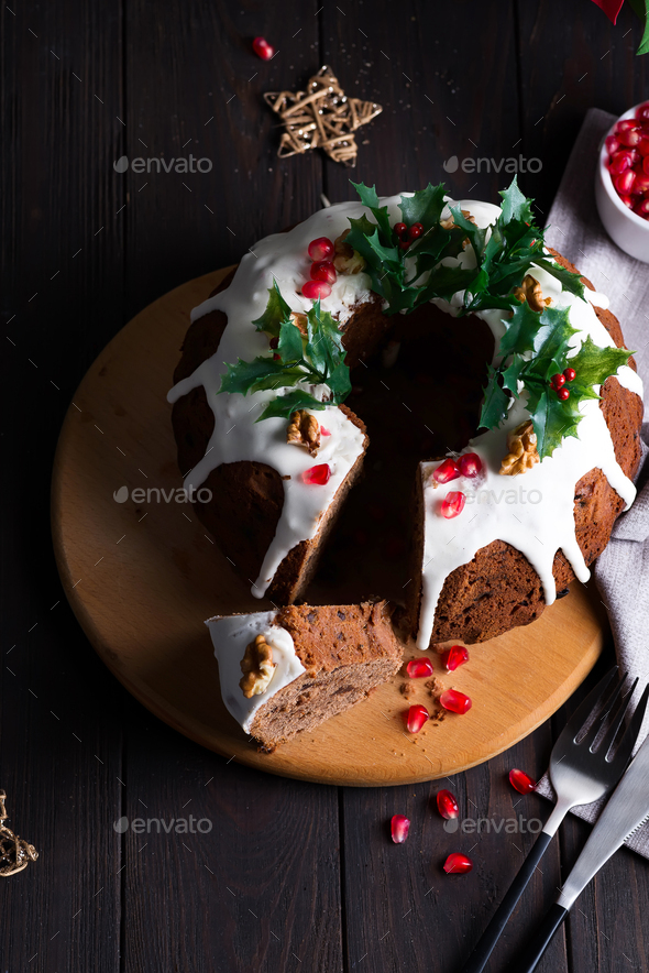 Christmas sliced chocolate cake with white icing, holly branches and pomegranate kernels on a wooden - Stock Photo - Images
