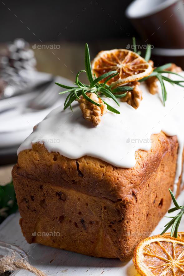 Fruit cake dusted with icing, nuts and dry orange close-up. Christmas and Winter Holidays homemade - Stock Photo - Images