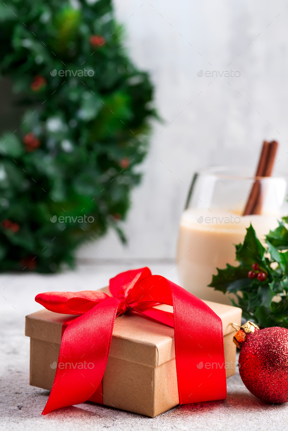 Beautiful gold present box with red bow and ribbons, ball, eggnog and holly berry branches on the - Stock Photo - Images