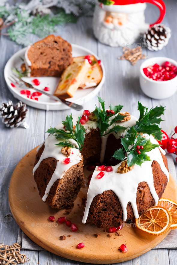 Christmas sliced chocolate cake with white icing, holly branches and pomegranate kernels on a gray - Stock Photo - Images