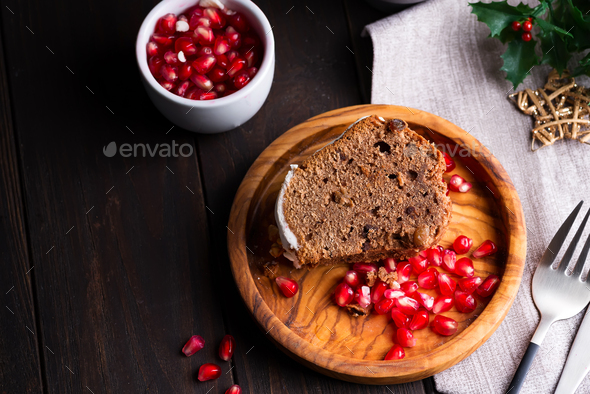 Christmas sliced chocolate cake with white icing and pomegranate kernels on a wooden dark background - Stock Photo - Images