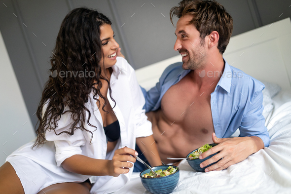 Cheerful young couple having breakfast in bed - Stock Photo - Images