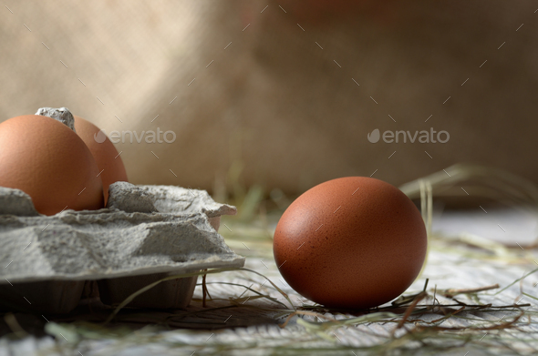 Raw organic brown chicken eggs in eco friendly paper carton on w - Stock Photo - Images