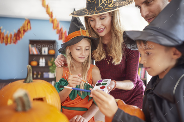 Kids with parents painting Halloween pumpkins - Stock Photo - Images