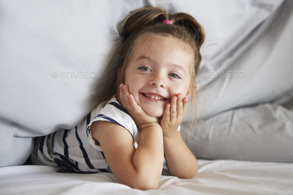 Cute girl under the duvet - Stock Photo - Images