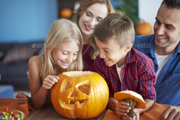 Family with scary Halloween pumpkin - Stock Photo - Images