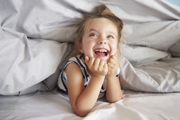 Girl having fun in her bed - Stock Photo - Images