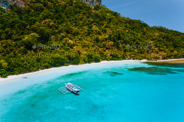 Aerial view of boat moored at secluded tropical beach with white sand, turquoise colored ocean - Stock Photo - Images