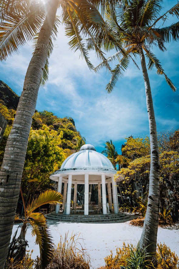 Abandoned Matinloc Shrine between two palm trees at the western coast of Matinloc Island at Palawan - Stock Photo - Images
