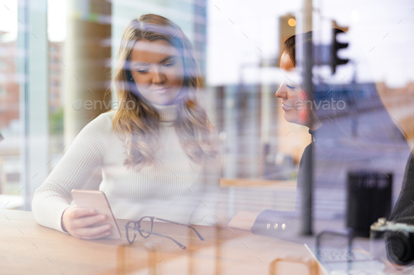 Two Friends Looking At Smartphone In Cafe seen through window - Stock Photo - Images