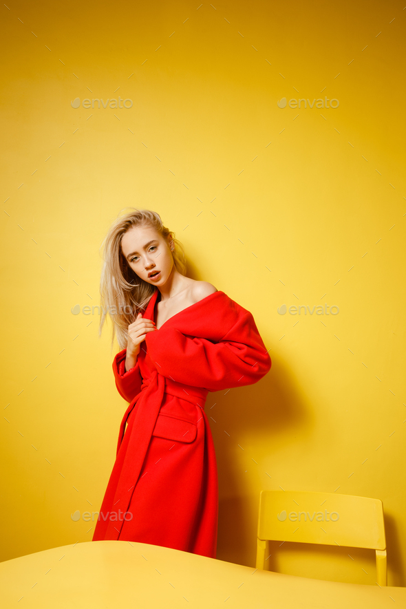 Fashion girl blogger dressed in stylish red coat is standing by the yellow table on the background - Stock Photo - Images