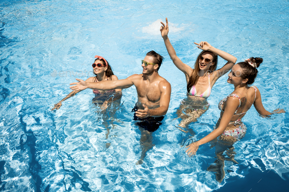 Company of young merry girls and guy are having fun in the swimming pool on the open air on a sunny - Stock Photo - Images