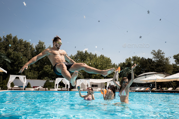 Company of young merry girls and guy relaxing in the swimming pool, jumping in the water and playing - Stock Photo - Images