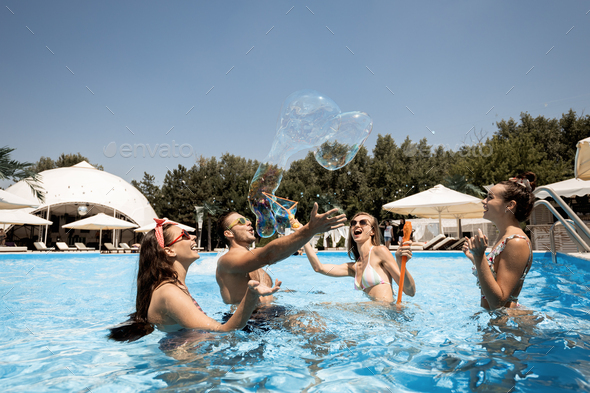 Company of young merry girls and guy are having fun in the swimming pool inflate huge soap bubbles - Stock Photo - Images