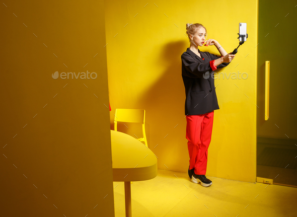 Fashion young girl blogger dressed in red trousers and black jacket takes a selfie on her smartphone - Stock Photo - Images