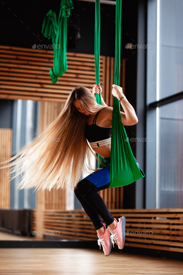 Young beautiful girl with long blond hair dressed in the sport clothes is doing fitness on the green - Stock Photo - Images