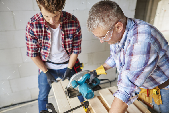 Carpenter cuts wooden planks with jigsaw - Stock Photo - Images