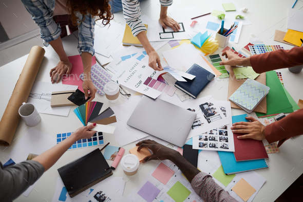Creative Designers Discussing Production over Table - Stock Photo - Images