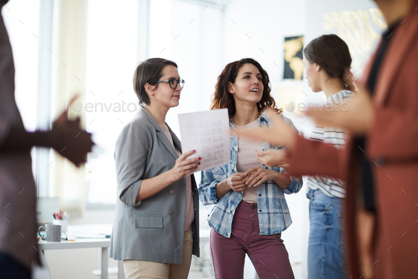 Creative Designers Discussing Project in Crowded Room - Stock Photo - Images