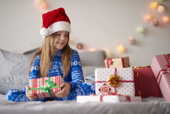 Cute little girl in bed with Christmas presents - Stock Photo - Images