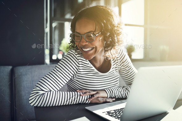 Young African woman laughing while browsing online with a laptop - Stock Photo - Images