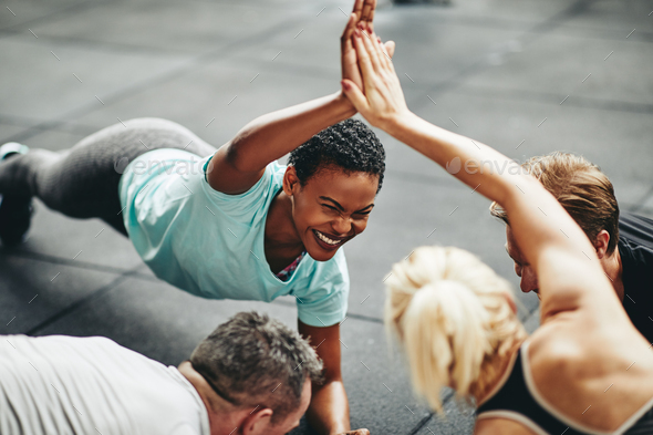 Laughing women high fiving while planking in a gym class - Stock Photo - Images