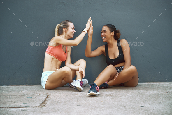 Laughing friends high fiving during a break from their workout - Stock Photo - Images