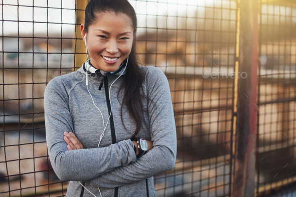 Young Asian woman in sportswear smiling while standing outside - Stock Photo - Images