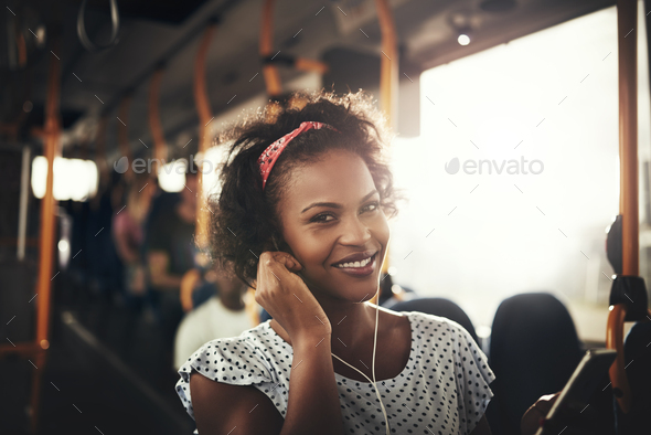 Smiling African woman standing on a bus listening to music - Stock Photo - Images