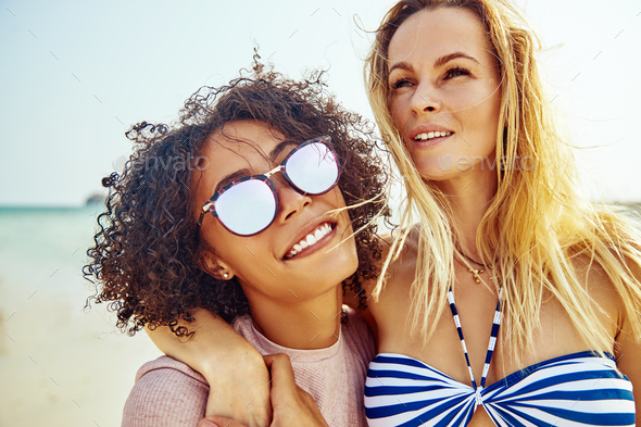Smiling female friends walking together along a beach in summer - Stock Photo - Images