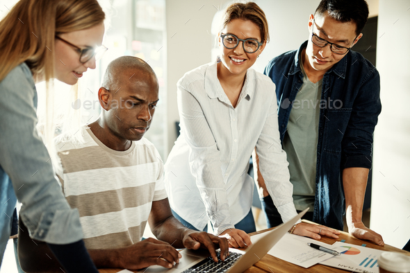 Diverse businesspeople talking together over a laptop in an office - Stock Photo - Images