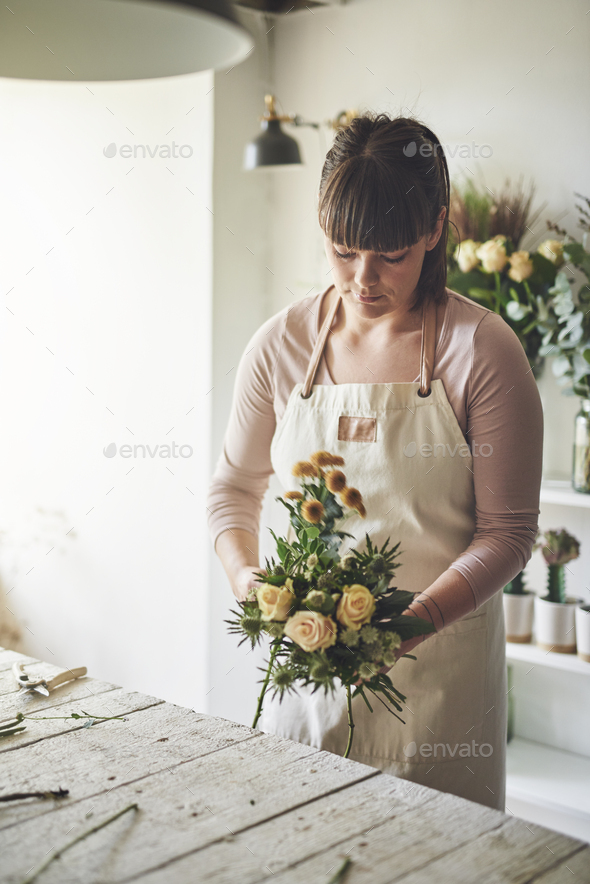 Young female florist making a flower bouquet in her workshop - Stock Photo - Images