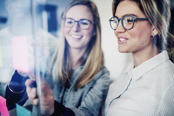Two businesswomen brainstorming with sticky notes on a glass wall - Stock Photo - Images