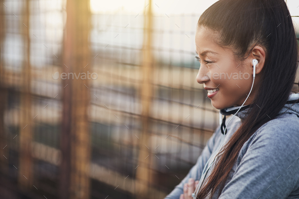 Asian woman listening to music while out for a run - Stock Photo - Images