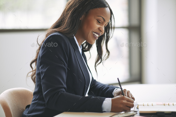 Smiling African American businesswoman writing notes in her day planner - Stock Photo - Images