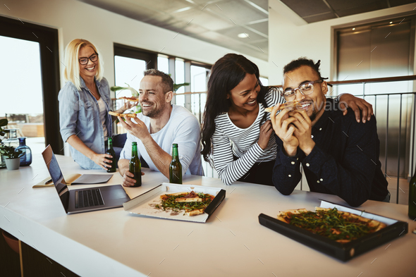 Diverse coworkers laughing and having pizza and beer after work - Stock Photo - Images