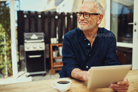 Smiling senior man sitting outside with a coffee and tablet - Stock Photo - Images