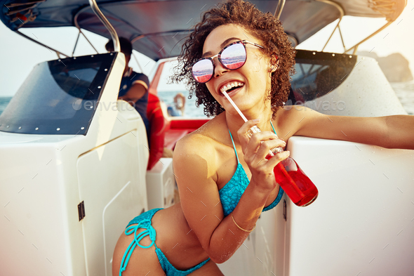 Smiling woman wearing her bikini having drinks on a boat - Stock Photo - Images