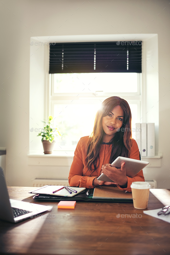 Confident young woman using a tablet in her home office - Stock Photo - Images