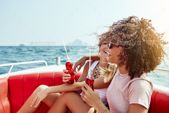 Laughing friends enjoying drinks while sitting on a boat - Stock Photo - Images