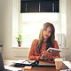 Confident young woman using a tablet in her home office - PhotoDune Item for Sale