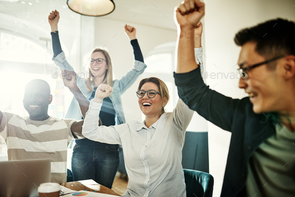 Diverse group of ecstatic colleagues cheering together in an office - Stock Photo - Images