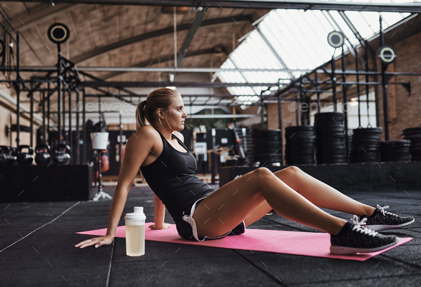 Young woman sitting on a gym floor before working out - Stock Photo - Images