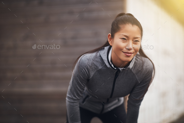 Young Asian woman in sportswear preparing for an outdoor run - Stock Photo - Images