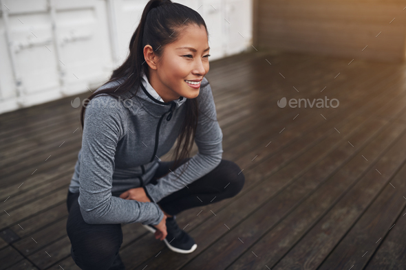 Smiling Asian woman crouching on the ground outdoors before jogging - Stock Photo - Images