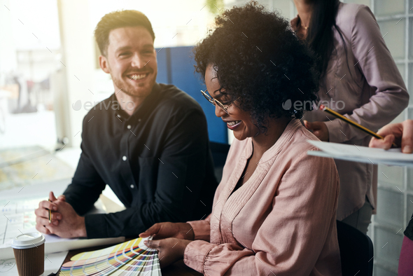 Smiling designers discussing color swatches together at an office desk - Stock Photo - Images